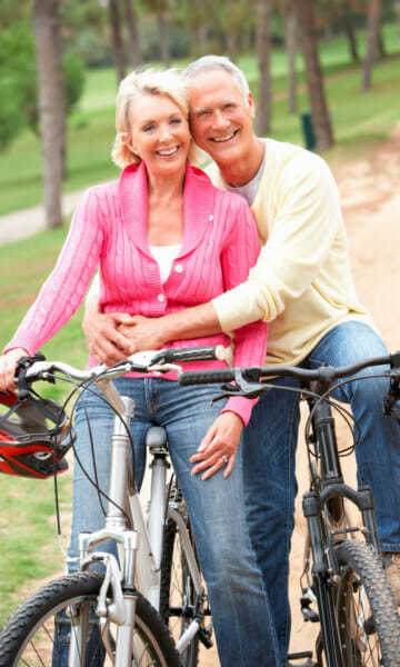Older couple out riding mountain bikes stopping to pose for a photo - Blocked Leg Arteries Page Image