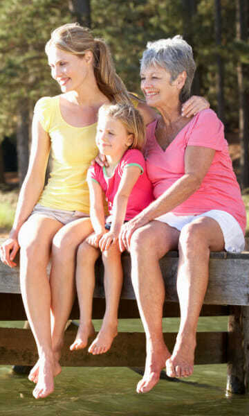 Grandma, Mum and Daughter sitting on a pier swinging their bare legs and ankles over the edge.