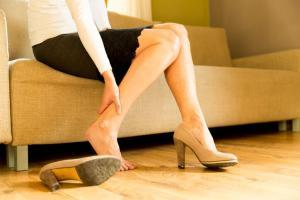 Woman rubs varicose vein on leg after taking off shoes